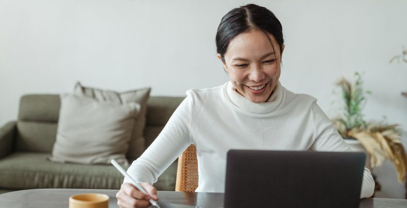woman sitting in front of zoom meeting on laptop taking notes